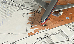 A printed aeronautical map with a figure of a plane on top of it.