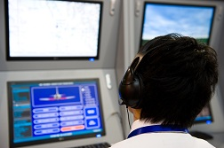 A flight controller looking at screens in a flight control tower.