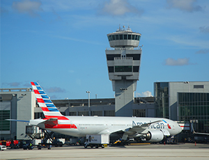 An American Airlines plain waits in front of a control tower at Miami International Airport.