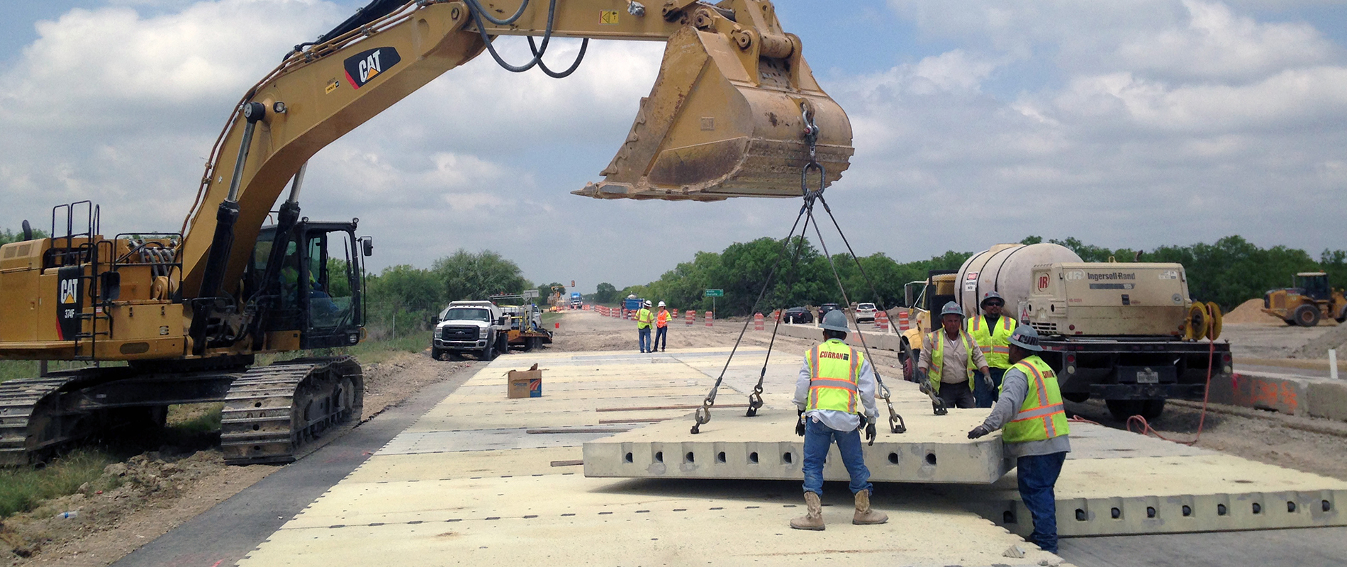 Workers install precast concrete pavement.
