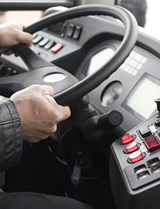 A bus driver's hands on a steering wheel