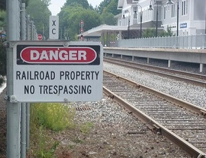 "A set of parallel railroad tracks in a residential area with a sign that warns ""Danger: Railroad Property. No Trespassing."""