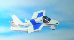 A small airplane in flight that can also be driven on roads.