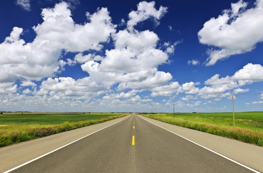 A long stretch of flat highway in the Canadian Saskatchewan prairies.