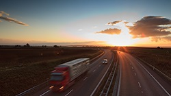 Image of a truck driving down a highway at dusk