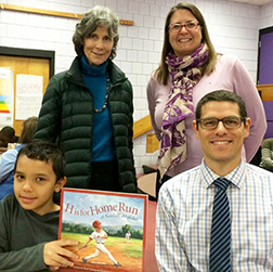 An elementary school student holds up a book as he sits beside his Volpe Lunch Buddy and two school staff members.