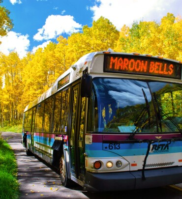 Image of bus with Maroon Bells on bus screen and yellow foliage in the background.