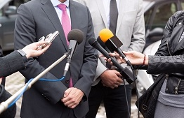 Several reporters hold their microphones outstretched, interviewing a man wearing a suit.