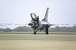 A U.S. Airforce pilot climbs into a military plane cockpit.