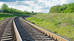 An image of a rail curving into the horizon with cloudy blue sky.
