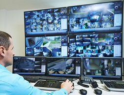 A security officer watches surveillance video on multiple monitors.