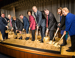 Event speakers hold shovels over sand for a ceremonial groundbreaking event. (Linda Haas Photography)