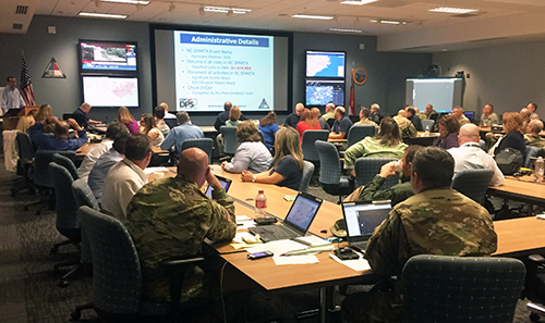A large conference room is filled with National Guard members and other emergency response staff who are working on laptops while also viewing a presentation at the front of the room.