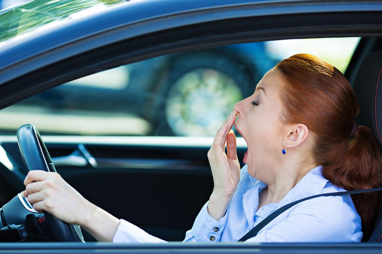 Woman yawing while driving a car.