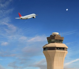 Air traffic control tower with plane in background.