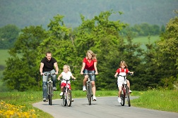 A family of four out on a bike ride down a bike path.