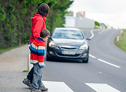 A car approaches a mother and son crossing a road at a crosswalk.