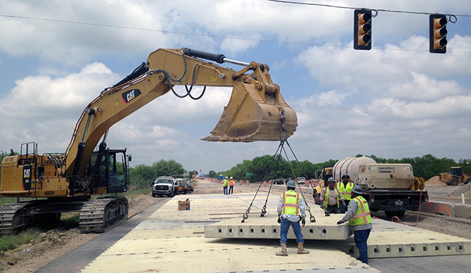 Workers install precast concrete pavement