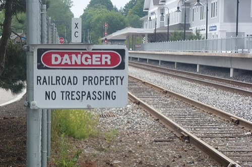 "A set of parallel railroad tracks in a residential area with a sign in the foreground that warns ""Danger: Railroad Property. No Trespassing."""