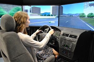 Female sits behind the wheel of Volpe's driving simulator.
