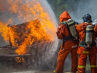 Two firefighters battling a fire with water.