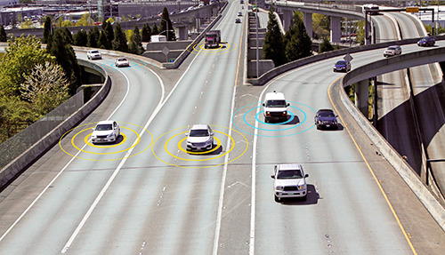 Depiction of several cars on a highway communicating with one another using V2V technology.