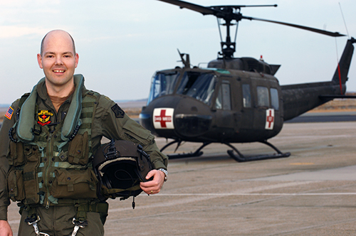 Seamus McGovern wearing military gear in front of a UH-IV MEDEVAC Huey helicopter.
