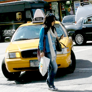 A woman crosses the street in front of a taxi while looking at her phone.