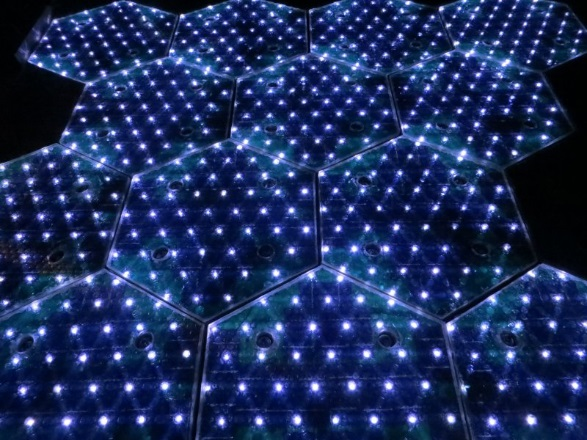 Lit up, hexagonal solar roadway panels.