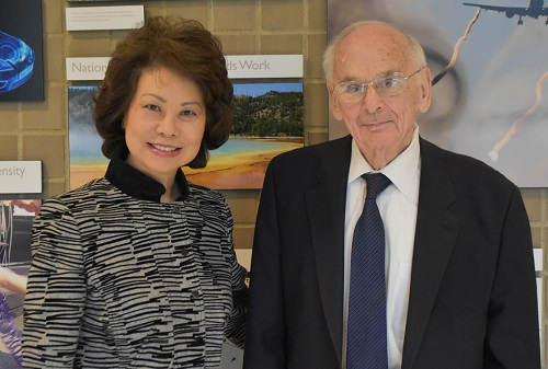 U.S. Secretary of Transportation Elaine Chao and Dr. Richard John stand together at the Volpe Center in front of a picture wall depicting Volpe's project work.