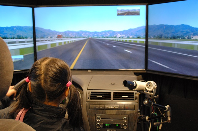 A girl sits in the seat of Volpe's car simulator with her hands on the wheel, navigating through a driving scenario.