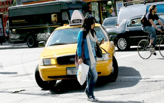 A woman crosses the street in front of a taxi cab while looking at her cell phone.