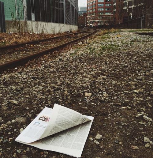 An open newspaper beside a set of railroad tracks