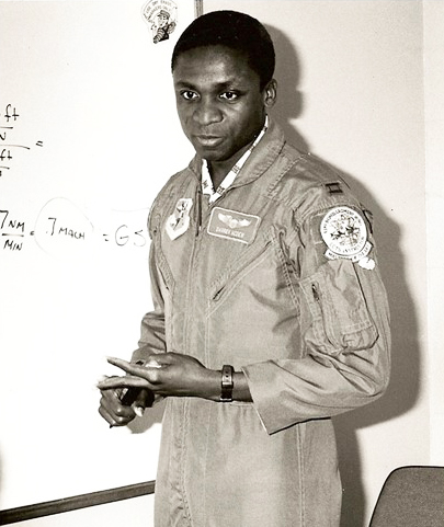 Black and white photo of General McDew standing at a white board with equations on it, instructing a class.