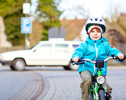 A young boy riding a bike near a car.