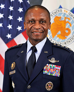General Darren McDew stands in military uniform in front of an American flag