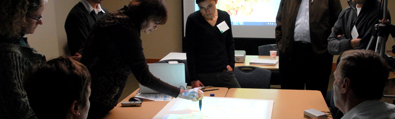 Staff are gathered around a map on a large planning table, engaged in dialog.
