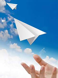 A hand tosses paper airplanes into the sky. (jannoon028/123RF photo)